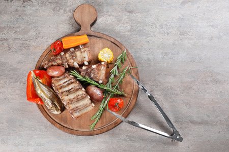 Wooden board with grilled ribs and vegetables on table Stock fotó