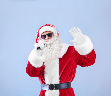 Santa Claus singing Christmas songs on light background