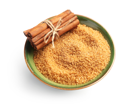 Bowl with cinnamon sugar and sticks on white background