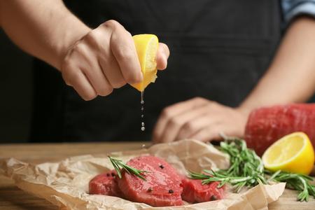 Chef-kok die vlees op tafel kookt