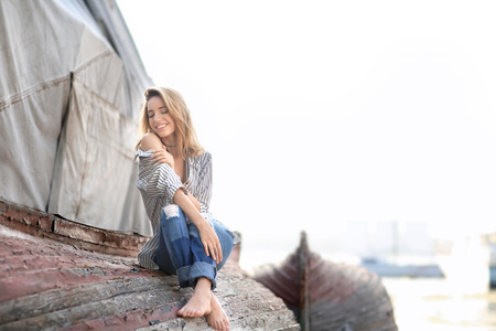 Young woman sitting on old overturned boat outdoors 版權商用圖片