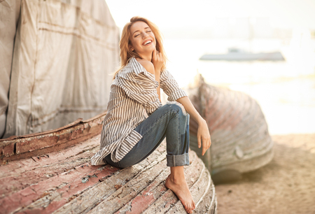 Young woman sitting on old overturned boat outdoors Stock Photo