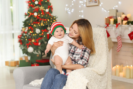 Happy young mother with baby in decorated room for Christmas