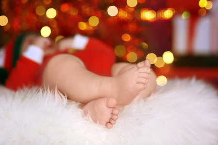 Cute little baby sleeping against blurred Christmas lights background