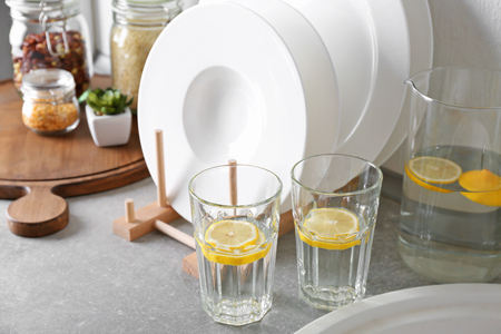 Set of white ceramic plates and fresh lemonade on kitchen counter