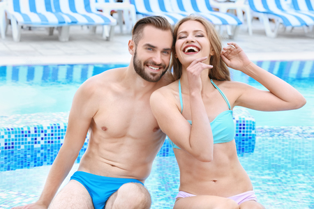 Happy young couple sitting near swimming pool Imagens