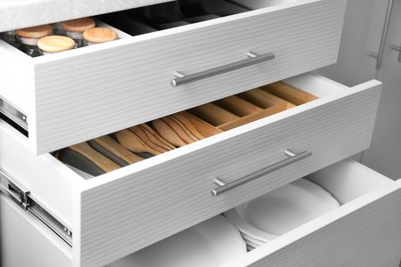 Set aus Keramikplatten und Utensilien in Küchenschubladen