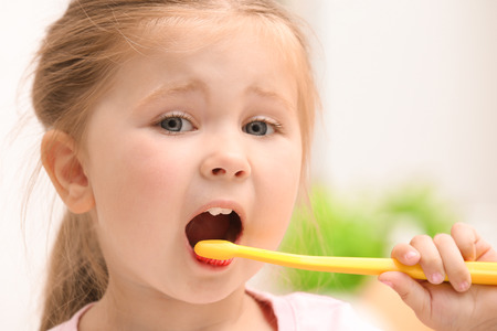 Cute little girl brushing teeth on blurred background