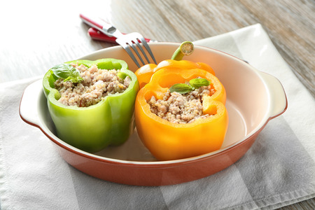 Quinoa stuffed peppers in casserole dish on dinner table Imagens