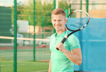 Young man with tennis racket on court Banque d'images