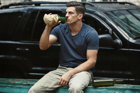 Man drinking alcohol near car Stockfoto