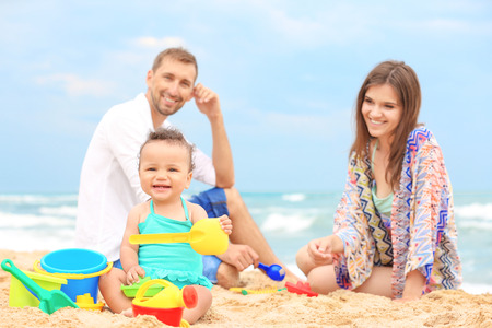 Happy couple with little daughter on beach