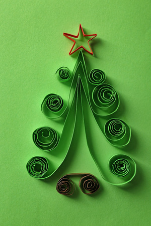 Christmas tree made of paper on green background