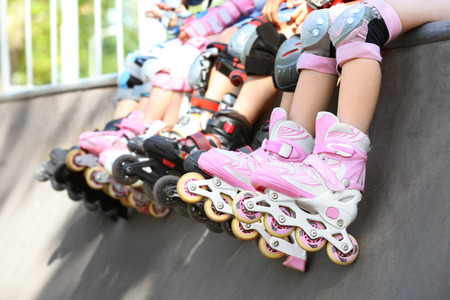 Legs of children on rollers at skate park Stock Photo