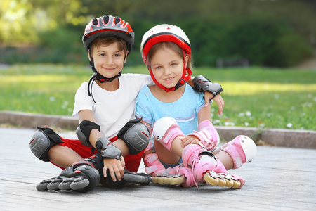 Cheerful boy and girl on roller skates sitting in park Banque d'images