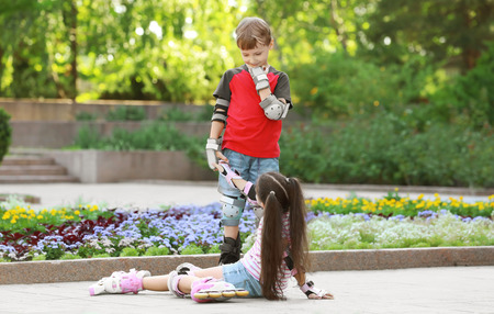 Cute boy on roller skates helping girl to get up in park