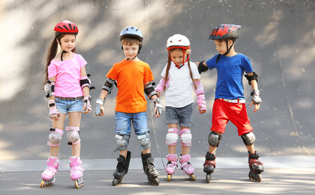 Cute children on rollers in skate park