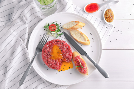 Delicious steak tartare with yolk on plate Imagens