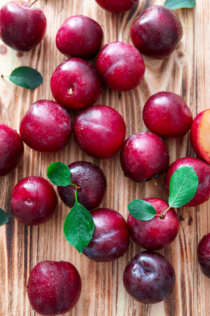 Fresh ripe plums on wooden table
