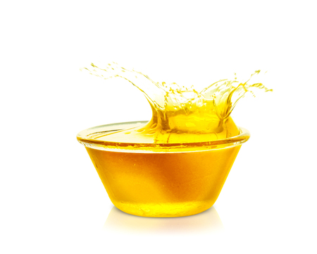 Cooking oil splashing from bowl, isolated on white 스톡 콘텐츠