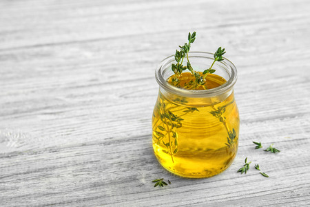 Oil with thyme in glass jar on light wooden background