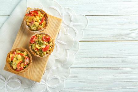 Delicious crispy tarts with broccoli on wooden board