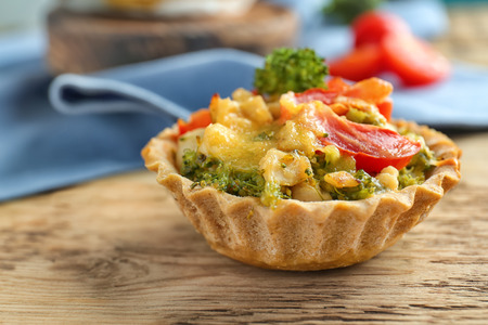 Delicious crispy tart with broccoli on wooden table