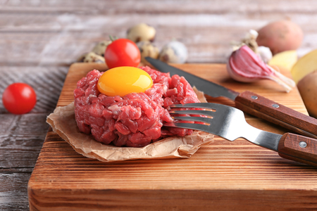 Delicious steak tartare with yolk on wooden board