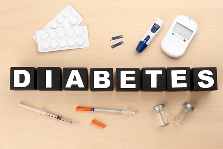 Composition with medical stuff and word Diabetes made of cubes on wooden background