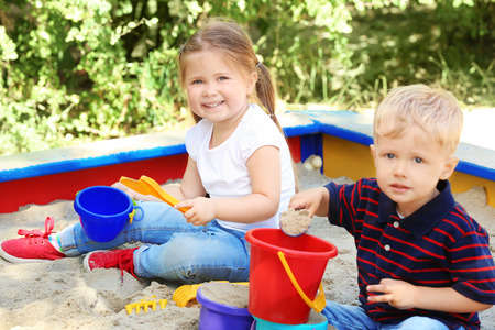 Cute little children playing in sandbox, outdoors Stock Photo