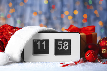 Digital alarm clock with Santa hat and decorations against defocused lights. Christmas countdown concept