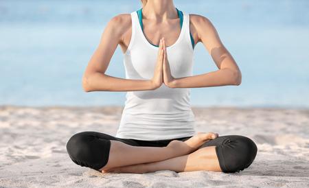 Beautiful young woman practicing yoga on sea beach 版權商用圖片