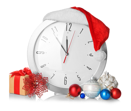 Clock with Santa hat and decorations on white background. Christmas countdown concept 免版税图像