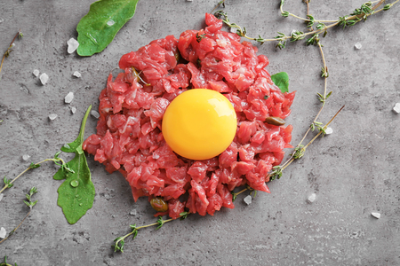Delicious steak tartare with yolk and herbs on table Imagens