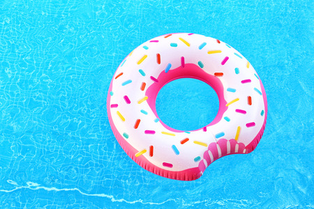 Colorful inflatable donut in blue swimming pool