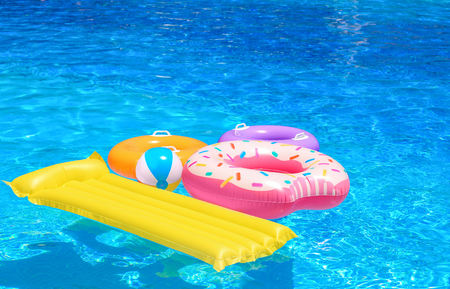 Inflatable rings, mattress and ball in blue swimming pool Foto de archivo - 111615224