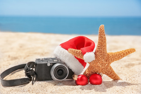 Santa hat with sea star, camera and decorations on beach. Christmas holidays concept