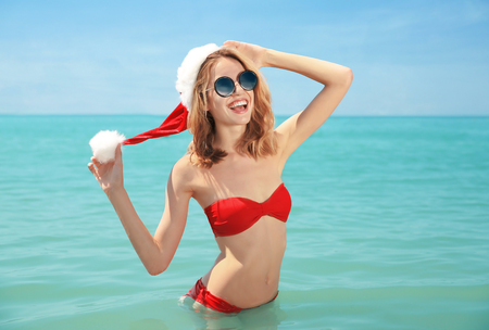 Young woman in Santa hat standing in water. Christmas holidays concept