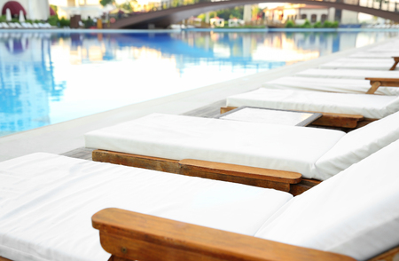Empty sunbeds near swimming pool in luxury hotel