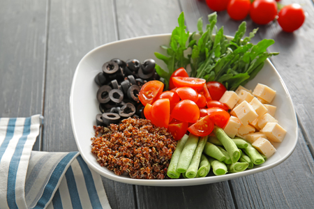 Plate with quinoa and vegetables on wooden background