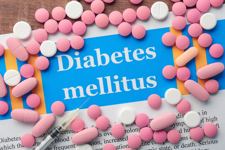 Pills and syringe for patients with diabetes on paper