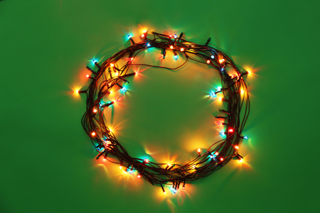 Circle of Christmas lights glowing on green background 免版税图像