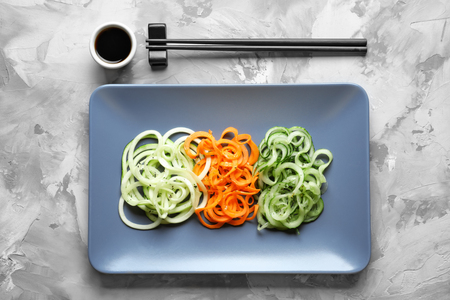 Plate with raw vegetable spaghetti and chopsticks on grunge background