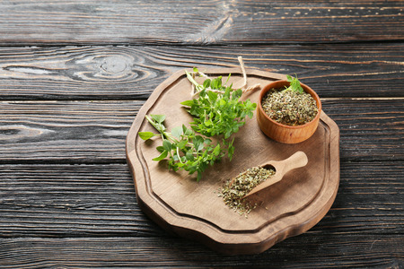 Beautiful composition with fresh and dried oregano on wooden board