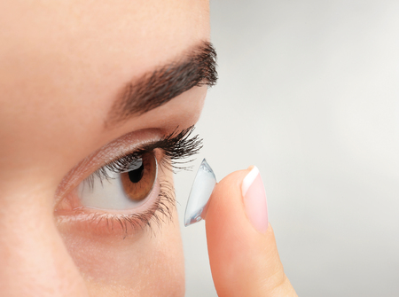 Young woman putting contact lens on light background, closeup