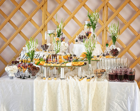 Wedding buffet table with different fruit desserts and drinks indoors