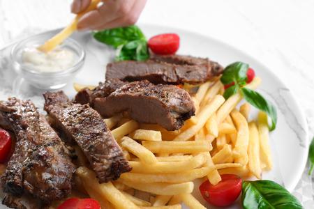 Piatto con deliziose bistecche alla griglia sul tavolo della cucina