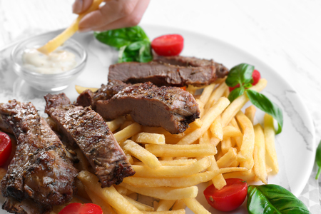 Plate with delicious grilled steak frites on kitchen table