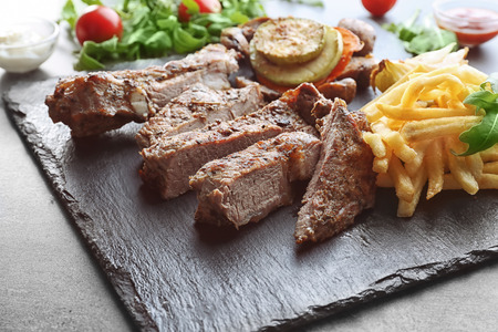 Delicious grilled steak frites on slate plate 스톡 콘텐츠