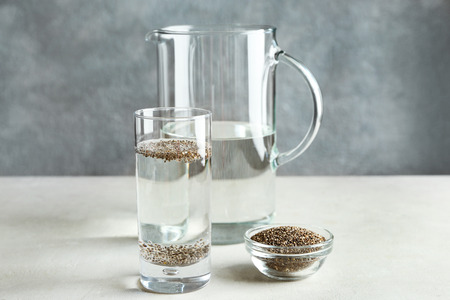Glass of water and bowl with chia seeds on table
